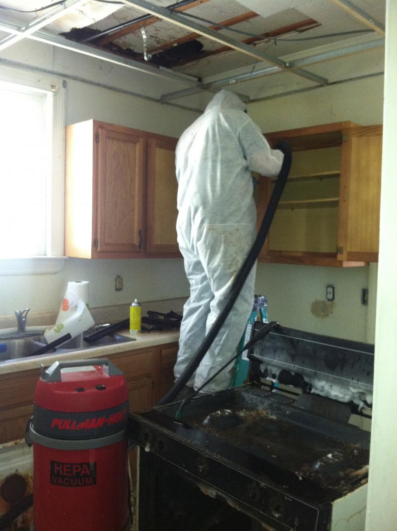 HEPA vacuuming cabinets in a meth house